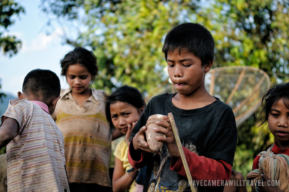 A boy wraps the string attached to a stick around the base of a spinning top. Luang Namtha province in northern Laos.