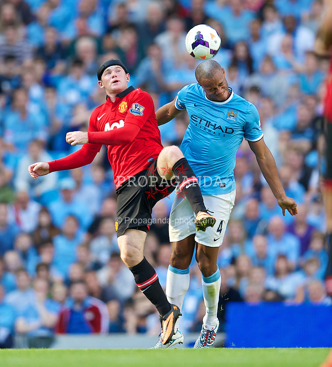 MANCHESTER, ENGLAND - Sunday, September 22, 2013: Manchester City's Vincent Kompany in action against Manchester United's Wayne Rooney during the Premiership match at the City of Manchester Stadium. (Pic by David Rawcliffe/Propaganda)