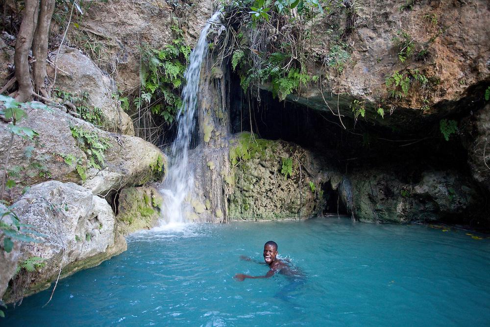 A boy swims in a pool near a spring providing a rare source of fresh water in Ile de La Gonave, Haiti