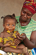 Jenneh Johnson, 31, feeds her daughter Jusu, 2, at home in the village of Julijuah, Bomi county, Liberia on Tuesday April 3, 2012. Jenneh has been receiving 2050 Liberian dollars (approx. 28 USD) per month since April 2010 through a UNICEF-sponsored social cash transfer programme. She says the money has allowed her to renovate the roof of her home, and send all her children to school. Before joining the programme only two of her children attended school.