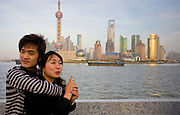 Young couple pose by the Pudong Financial District skyline at the Bund, Shanghai, China