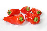 Group of mini red bell peppers on textured white background - fading to white on top