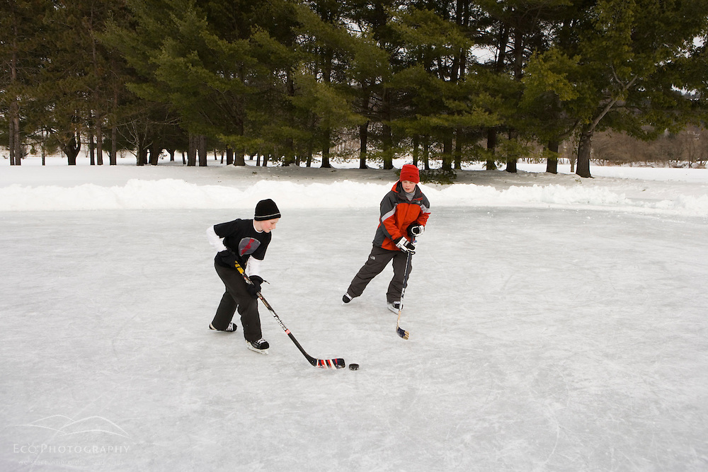 Boys playing hockey on a frozen pond in Quechee, Vermont. Model Release.