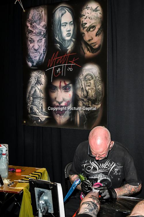 Matt K Tattoo tattoo a client at The Great British Tattoo Show, on 26 May 2019, London, UK.
