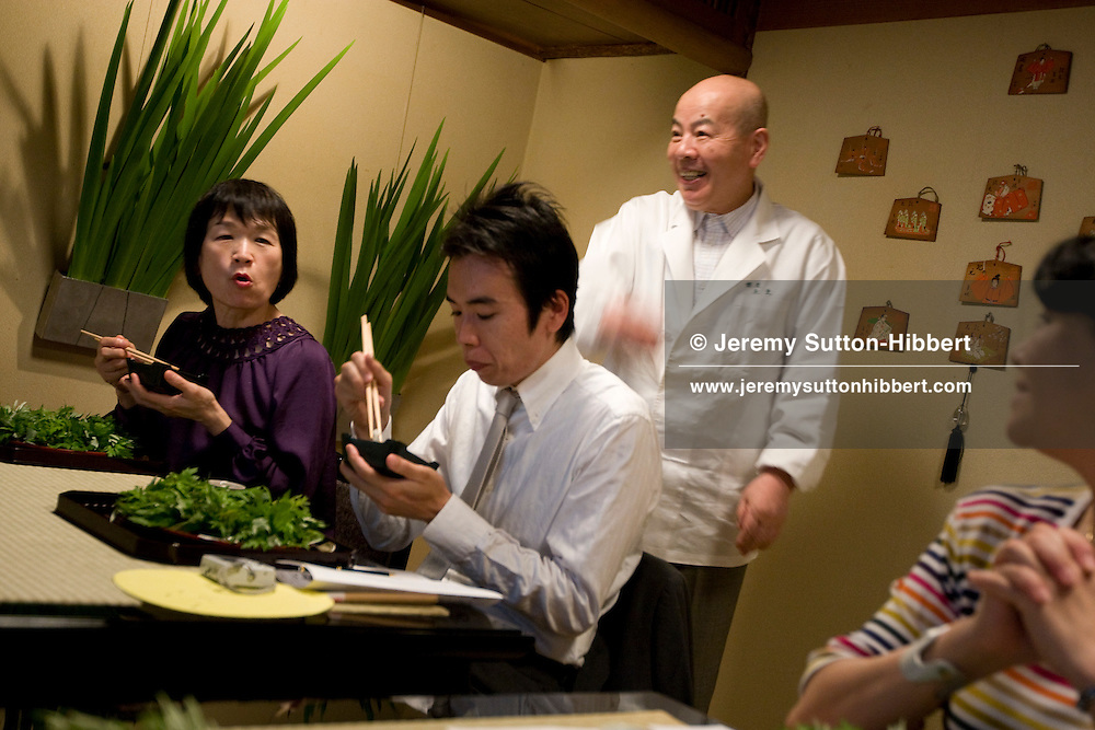 Guests appreciate their first course of food, surrounded on their plate by a wreath of Mogwart leaves, whilst Chef Hiroshi Ishida (centre, standing) welcomes them to the club, in the exclusive private dining club/restaurant 'Mibu' , owned by Chef Hiroshi Ishida (67yrs old) and wife Tomiko (63yrs old), in Ginza, Tokyo , Japan, Saturday 23rd May 2009.
