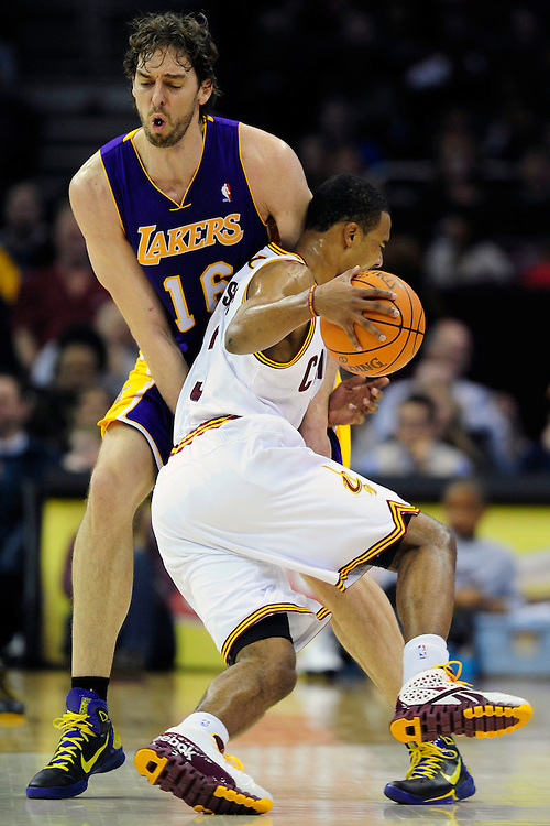 Feb. 16, 2011; Cleveland, OH, USA; Los Angeles Lakers power forward Pau Gasol (16) takes a hit from Cleveland Cavaliers point guard Ramon Sessions (3) during the first quarter at Quicken Loans Arena. Mandatory Credit: Jason Miller-US PRESSWIRE