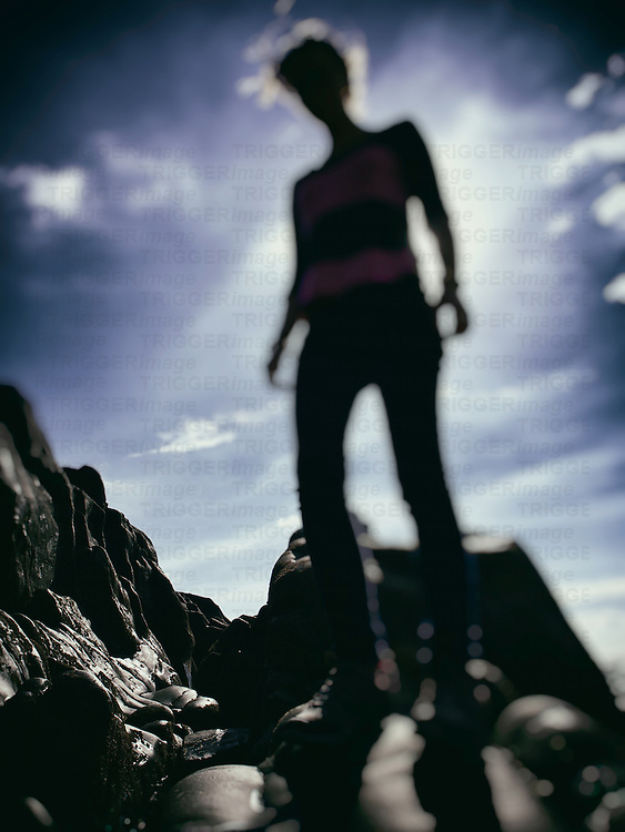 Teenage female standing on rocks with blue sky in summer