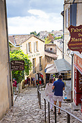 Tourists in cobbled street scene passing shops in the town of St Emilion, famous for wine production, France