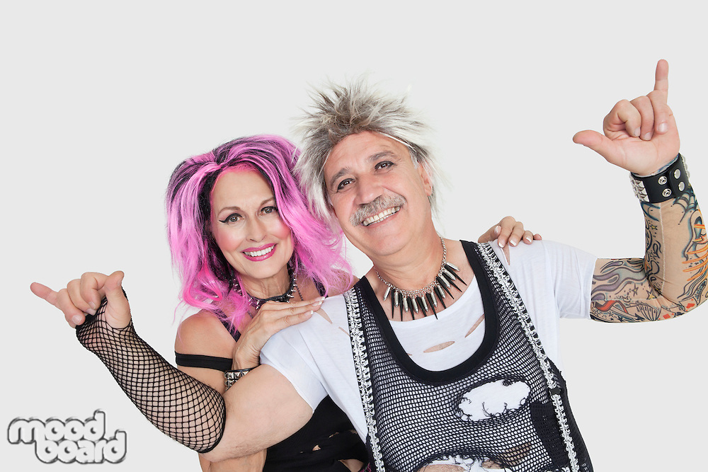 Portrait of senior punk couple over gray background