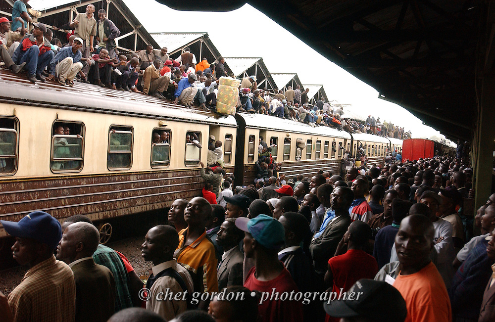 Kenyans pack an incoming railroad train arriving at Nairobi Railway Station on Monday, February 2, 2004. Thousands of Kenyans are effected by a limited numbered of matatus, buses and mini-buses on Kenya's roadways, as strict vehicle transportation safety laws went into effect yesterday.