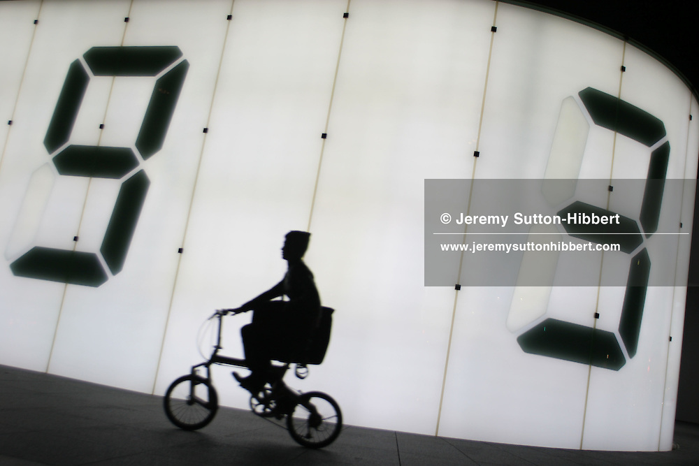 A cyclists passes a digital display on the wall of the TV Asahi building, in Roppongi district of Tokyo, Japan.