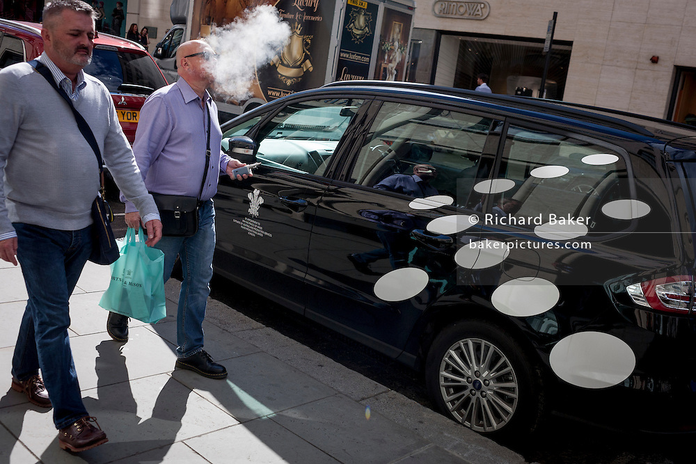 A smoker exhales a puff of cigarette smoke as he walks past a car featuring spots in New Bond Street, central London, England.