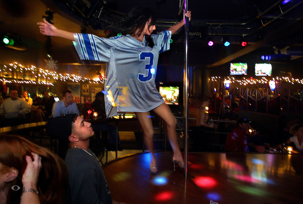 "Joey Harrington jersey on a dancer named Chelsea at the Toy Chest adult entertainment club in the Detroit area. It was given to her to dance in by Joey ""superfan"" Joey Saad (left, looking up) at a club frequented by Lions, Tigers and Red Wings players."
