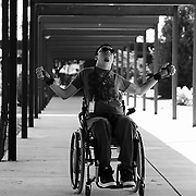 Ricky glides down a breezeway at the Woodrow Wilson Rehabilitation Center, in Fishersville, VA, practicing with a manual wheelchair.  Making the transition from a power wheelchair to a manual wheelchair represents a milestone in his rehabilitation process.