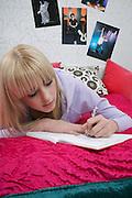 Portrait of teenage girl (16-17) lying on bed writing diary
