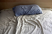 close up of unmade bed with rumpled head cushion sheets
