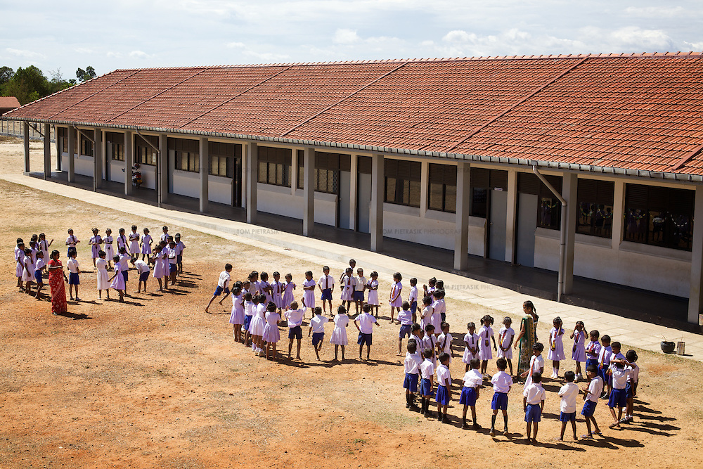 Students and staff play games outside their new school building.<br /> <br /> The Namahal Vidayalaya Government Tamil Mixed School serves the community living in the Navalady Tsunami Resettlement village in Batticaloa. All children attending the school were affected both by the tsunami and the conflict between the SLA (Sri Lankan Army) and the LTTE. The school has 434 students in Grades 1-11. UNICEF funded construction of the new school building, opened in June 2008 and provides teacher training in Child Friendly Schooling. UNICEF have also helped in the drawing up of a School Development Plan. <br /> <br /> The old school building was situated close to the coastline and was completely destroyed in the tsunami. A total of 119 students lost their lives. UNICEF supplied three Temporary Learning Spaces during the transition period before completion of the new school building. The new building boasts bright, well ventilated learning spaces and an auditorium. There are some concerns over sourcing materials for repairs to worn fixtures and fittings, for example the doors which are made of metal rather than locally available wood.  <br /> <br /> Photo: Tom Pietrasik<br /> Batticaloa District, Sri Lanka<br /> October 1st 2009