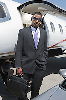 African-American businessman standing in front of private airplane and car.