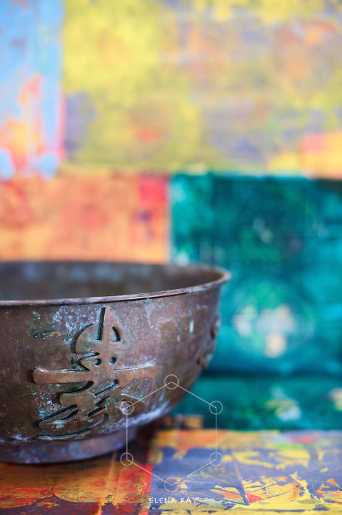 Still Life Photography. Metal bowl carved with asian calligraphy.