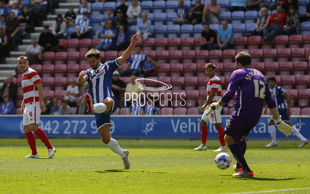 Grigg closes down O'Donnell during the Sky Bet League 1 match between Wigan Athletic and Doncaster Rovers at the DW Stadium, Wigan, England on 16 August 2015. Photo by Simon Davies.