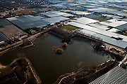Nederland, Zuid-Holland, Westland, 20-03-2009; hartje Westland, kassen rond de waterplas 'Prinsenbos' gezien naar bebouwing van Naaldwijk (Gemeente 's-Gravezande). Air view on glasshouses in the heart of the horticultural area and a pond called Prinsenbos..Swart collectie, luchtfoto (toeslag); Swart Collection, aerial photo (additional fee required); .foto Siebe Swart / photo Siebe Swart