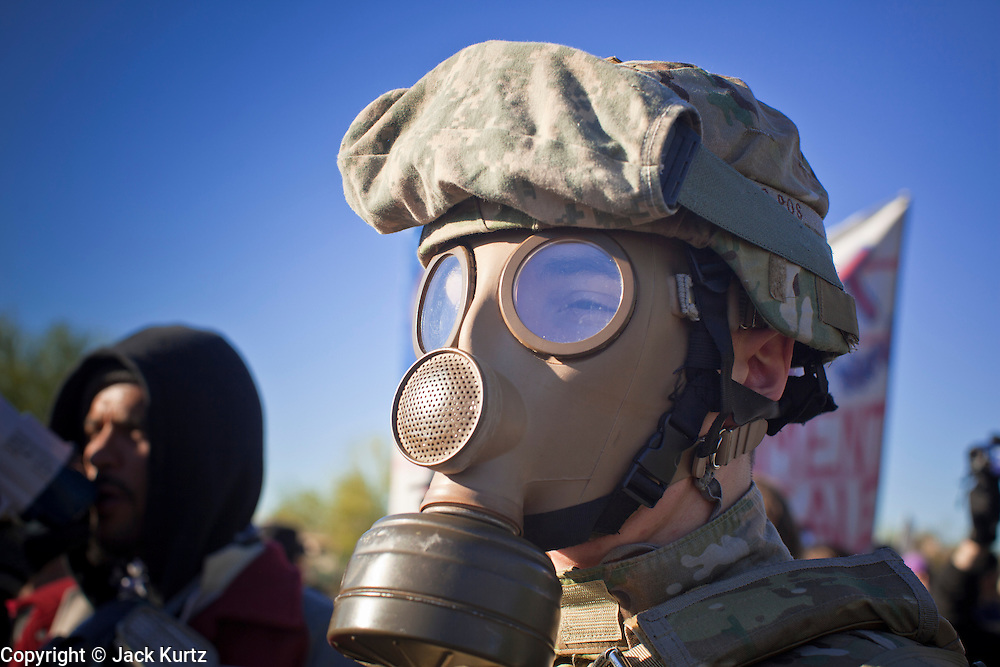 30 NOVEMBER 2011 - PHOENIX, AZ:    An anti-ALEC protester wearing a helmet and gas mask in front of the Westin Kierland Resort and Spa Wednesday. About 300 people picketed the American Legislative Exchange Council (ALEC) conference at the Westin Kierland Resort and Spa in Phoenix, AZ, Wednesday. The protesters claim ALEC, a conservative think tank, violates its tax exempt status by engaging in lobbying, a charge ALEC officials deny. Many conservative pieces of legislation, like Arizona's anti-immigration bill SB1070, originate with ALEC conferences (SB 1070 originated at an ALEC conference several years ago). Many of the protesters are also members of the Occupy movement.   PHOTO BY JACK KURTZ