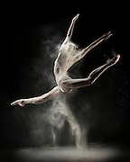 Contemporary female dancer, Ashley Mayeux, jumping with white flour. Taken in the photo studio on a black background. Photograph taken in New York City by photographer Rachel Neville.