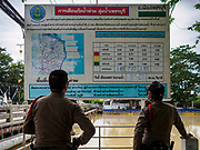 09 AUGUST 2018 - PHETCHABURI, PHETCHABURI, THAILAND: Thai police officers look at a chart of flood and river levels for the Phetchaburi River in Phetchaburi town. The Phetchaburi River flows from Kaeng Krachan Dam to the Gulf of Siam through several towns including Ban Lat, Phetchaburi (the capital of Phetchaburi province) and Ban Laem. Government officials have warned residents of those towns that their towns will flood because the reservoir behind the dam is approaching capacity. Ban Lat and Phetchaburi could be flooded for several weeks. Residents of Ban Laem have been warned that their community could be inundated for over a month. Dams in Kanchanaburi province, west of Phetchaburi, are also approaching capacity and flooding is also expected in that area.   PHOTO BY JACK KURTZ