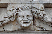Mask and garland frieze from the Portico of Tiberius on the Southern portico of the Agora, 1st century AD, Aphrodisias, Aydin, Turkey. The Sculpture School at Aphrodisias was an important producer of carved marble sarcophagi and friezes from the 1st century BC until the 6th century AD. The Portico of Tiberius was built under the reign of Tiberius and has many examples of mask and garland friezes, consisting of the heads of gods, goddesses, theatrical characters, mythological figures or masks, each with a distinct facial expression, between hanging garlands of leaves, fruit and flowers. This example shows an extremely lifelike laughing man, possibly representing drunkenness. Aphrodisias was a small ancient Greek city in Caria near the modern-day town of Geyre. It was named after Aphrodite, the Greek goddess of love, who had here her unique cult image, the Aphrodite of Aphrodisias. The city suffered major earthquakes in the 4th and 7th centuries which destroyed most of the ancient structures. Picture by Manuel Cohen