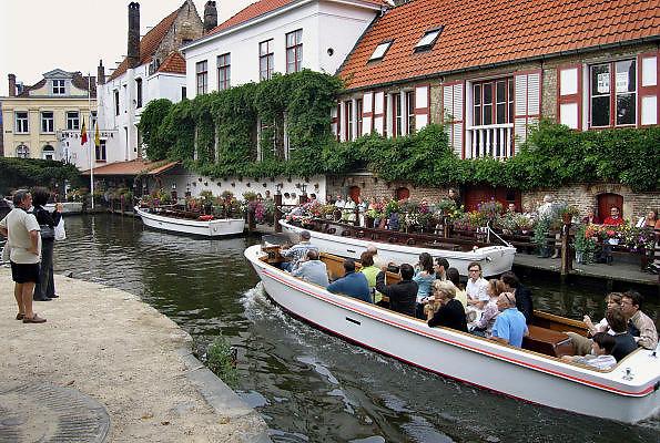 Belgie, Brugge, 3-9-2005..Toeristen laten zich op een ronvaartboot door de oude stad varen. Stadsgids. Architectuur, monumenten, stadsgezicht..Belgium, stedentrip, toerisme, tourism. Vakantie...Foto: Flip Franssen/Hollandse Hoogte