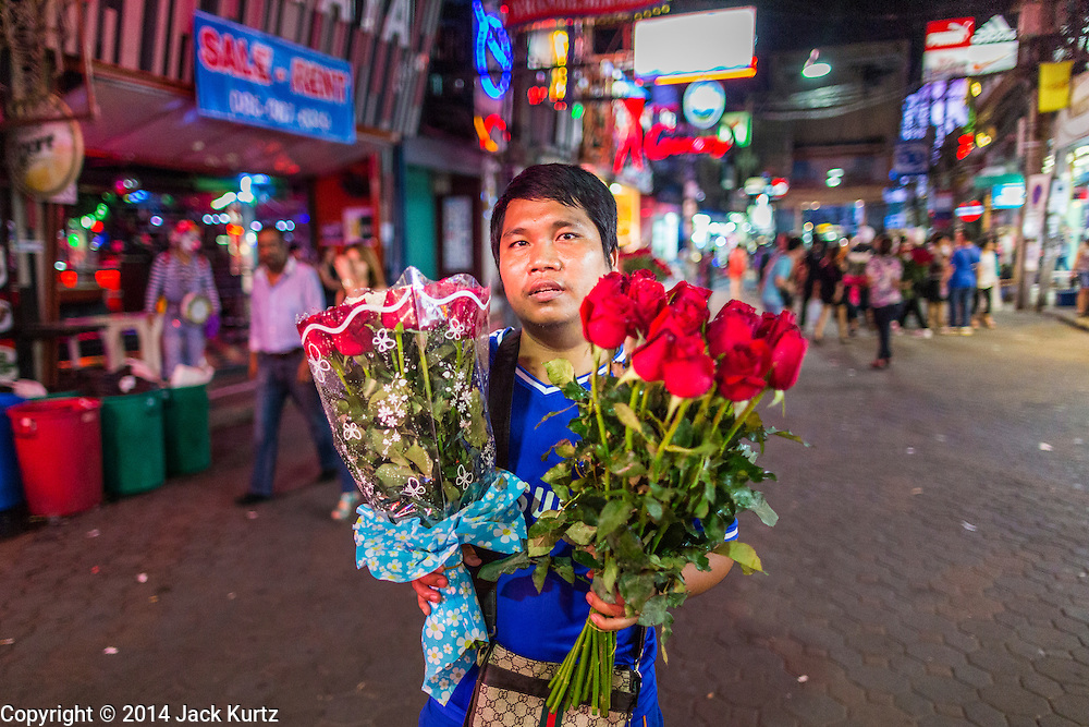 "26 SEPTEMBER 2014 - PATTAYA, CHONBURI, THAILAND: A man sells flowers on Walking Street in Pataya. Pataya, a beach resort about two hours from Bangkok, has wrestled with a reputation of having a high crime rate and being a haven for sex tourism. After the coup in May, the military government cracked down on other Thai beach resorts, notably Phuket and Hua Hin, putting military officers in charge of law enforcement and cleaning up unlicensed businesses that encroached on beaches. Pattaya city officials have launched their own crackdown and clean up in order to prevent a military crackdown. City officials have vowed to remake Pattaya as a ""family friendly"" destination. City police and tourist police now patrol ""Walking Street,"" Pattaya's notorious red light district, and officials are cracking down on unlicensed businesses on the beach.     PHOTO BY JACK KURTZ"