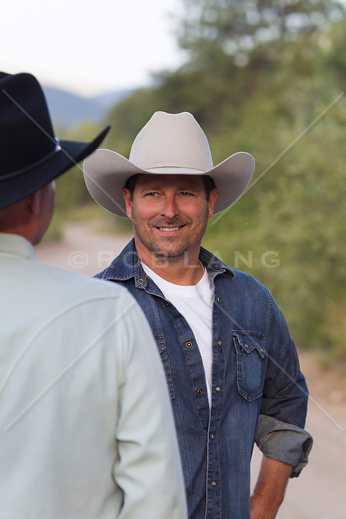 cowboy smiling at another cowboy outdoors