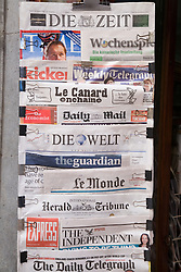 Spanish and international newspapers in a newsagent's stand,