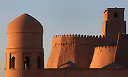 Detail of a turret of the main gate of Ichan-Kala, Ota Darvoza (Father Gate), on the left  and walls of the old city on the right distance, Khiva, Uzbekistan, pictured on July 7, 2010, at dawn. Khiva's old city, Ichan Kala, is surrounded by 2.2 kilometres of crenellated and bastioned city walls. Some sections may be 5th century, but the strongest sections were built 1686-88 by Arang Khan. The main gate today is the restored western Ota Darvoza (Father Gate). Khiva, ancient and remote, is the most intact Silk Road city. Ichan Kala, its old town, was the first site in Uzbekistan to become a World Heritage Site(1991). Picture by Manuel Cohen.