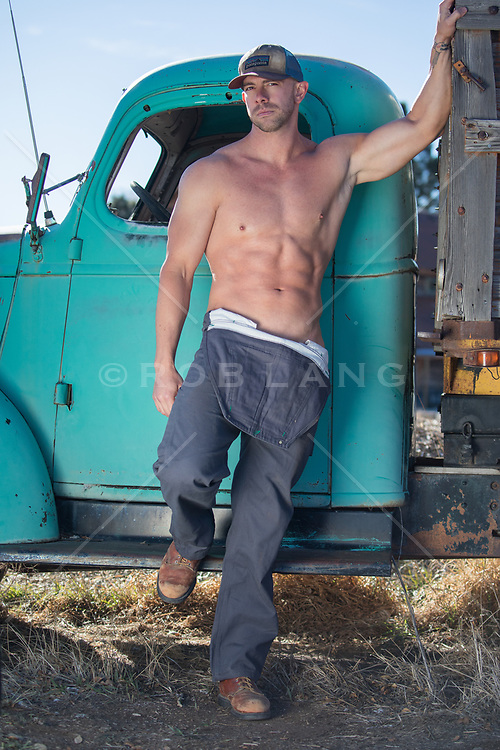 sexy shirtless trucker by an old truck