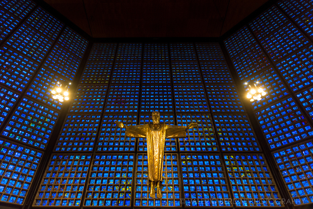 The Kaiser Wilhelm Memorial Church is a Protestant church located in Berlin on the Kurf&uuml;rstendamm in the centre of the Breitscheidplatz. Inside the church, opposite the entrance, is a figure of the crucifixus which is suspended above the altar. <br /> <br /> The original church on the site was built in the 1890s. It was badly damaged in a bombing raid in 1943. The present building, which consists of a church with an attached foyer and a separate belfry with an attached chapel, was built between 1959 and 1963. The damaged spire of the old church has been retained and its ground floor has been made into a memorial hall.
