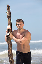 hot shirtless man with driftwood by the ocean