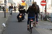 In Utrecht rijdt een motor op het drukke fietspad op de Amsterdamsestraatweg. <br /> <br /> In Utrecht a motor cycle rides on the bike lane.