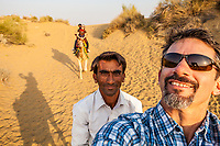 A caucasian tourist on a camel trek takes a selfie of himself and his driver as well as his wife on her camel with her driver in the background.