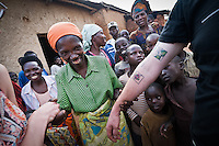 Stephen Vick, a buyer from Intelligentsia Coffee & Tea, shows off his tattoos of coffee cherries to locals in a small coffee growing village in Western Rwanda.