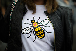 © Licensed to London News Pictures . 01/07/2017 . Manchester , UK . A woman wearing a worker bee t-shirt , the symbol of Manchester . Crowds enjoying the DJ sets ahead of the main act . Hacienda Classical play at the Castlefield Bowl as part of Sounds of the City , during the Manchester International Festival . A collaboration between DJs Mike Pickering and Graeme Park and the Manchester Camerata orchestra , Hacienda Classical reworks music by bands including the Happy Mondays and New Order and features Manchester musicians including Rowetta and Peter Hook . Photo credit : Joel Goodman/LNP