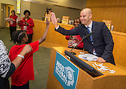 Pablo Alsina high-fives with a student during the reveal of the 32 finalists in the Houston ISD NCAA Read to the Final Four, November 11, 2015.