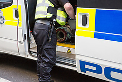 London, UK. 20th April 2019. A police officer places an arm tube used for a lock-on by Extinction Rebellion climate change activists at Oxford Circus into a police vehicle. The heart of London's shopping district was blocked until late afternoon by lock-ons on the sixth day of International Rebellion activities to call on the British government to take urgent action to combat climate change.