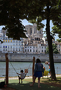 Child on a swing in a playground on the newly renovated pedestrianised section of the Voie Georges Pompidou, a West-East roadway across Paris, on the right bank of the river Seine, in the 4th arrondissement of Paris, France. In the distance are the towers of Notre Dame cathedral on the Ile de la Cite. The Cathedrale Notre-Dame de Paris, or Notre-Dame cathedral, was built 1163-1345 in French Gothic style. Picture by Manuel Cohen