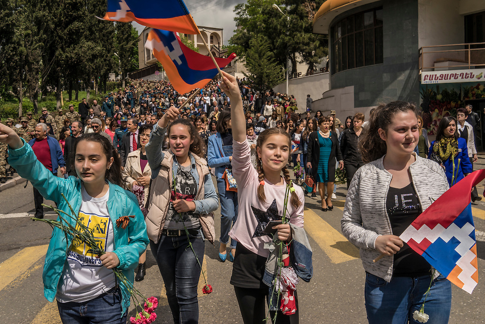 Girls waving flags of the Nagorno-Karabakh Republic take part in a march to commemorate both the victory over Nazi Germany in the Second World War as well as the date when the strategic town of Shushi was taken by Armenian forces from Azerbaijanis during the war in the 1990s on Monday, May 9, 2016 in Stepanakert, Nagorno-Karabakh.