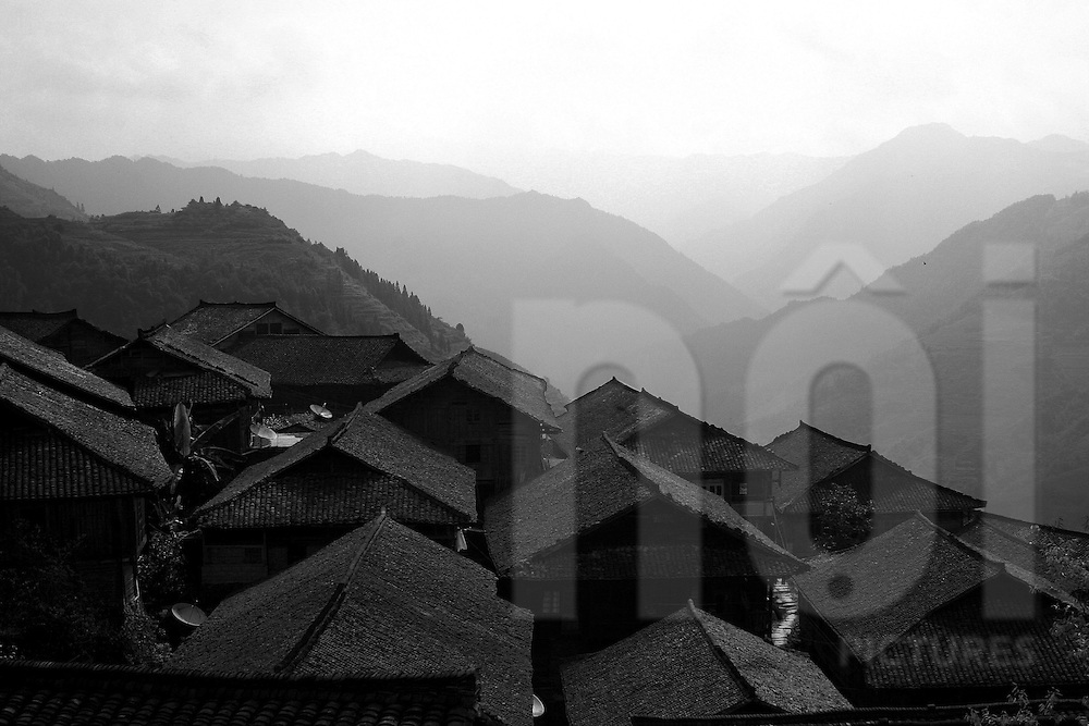 Roofs of a small village in Ping'an area with mountainous landscape in background. Guangxi, China, Asia
