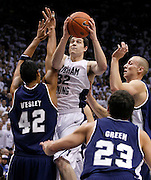Jimmer Fredette of BYU (32) attempts to score against Utah State defenders from left, Tai Wesley, Brian Green, and Brady Jardine during the first half of an NCAA basketball game, Nov. 17, 2010 in Provo, Utah. (AP Photo/Colin E Braley)