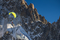 A single person paragliding next to the north face of Petit Dru above the city of Chamonix, Mont Blanc, France.