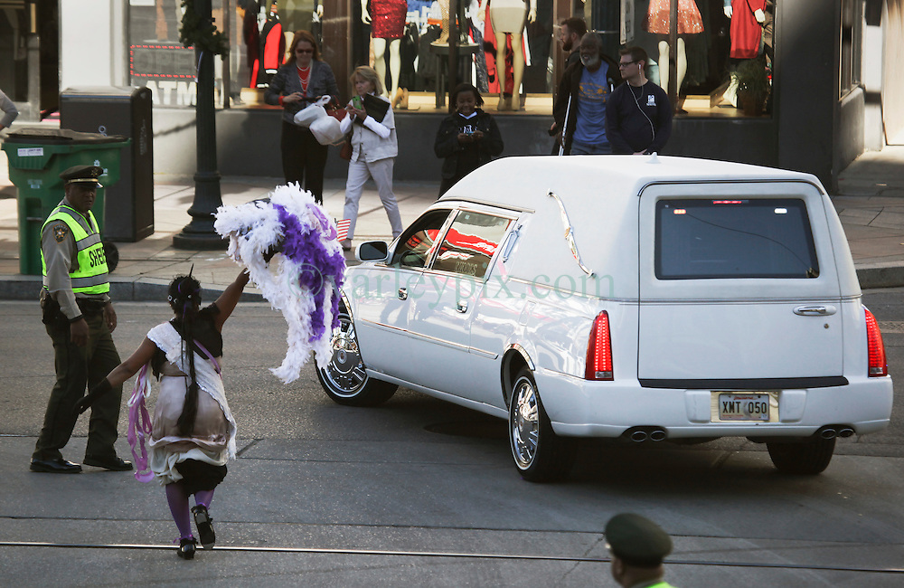 20 November 2015. Orpheum Theater, New Orleans, Louisiana. <br /> Memorial service for musician Allen Toussaint. A woman runs after the hearse as people  spill out of the Orpheum Theater in a second line procession following the touching memorial service for one of the city's most influential musicians. <br /> Photo; Charlie Varley/varleypix.com