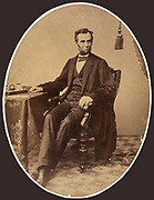 President Abraham Lincoln (1809-1865) in 1863, little more than a week before he gave the Gettysburg Address. Full-length oval portrait, seated with right arm resting on table, facing slightly right.